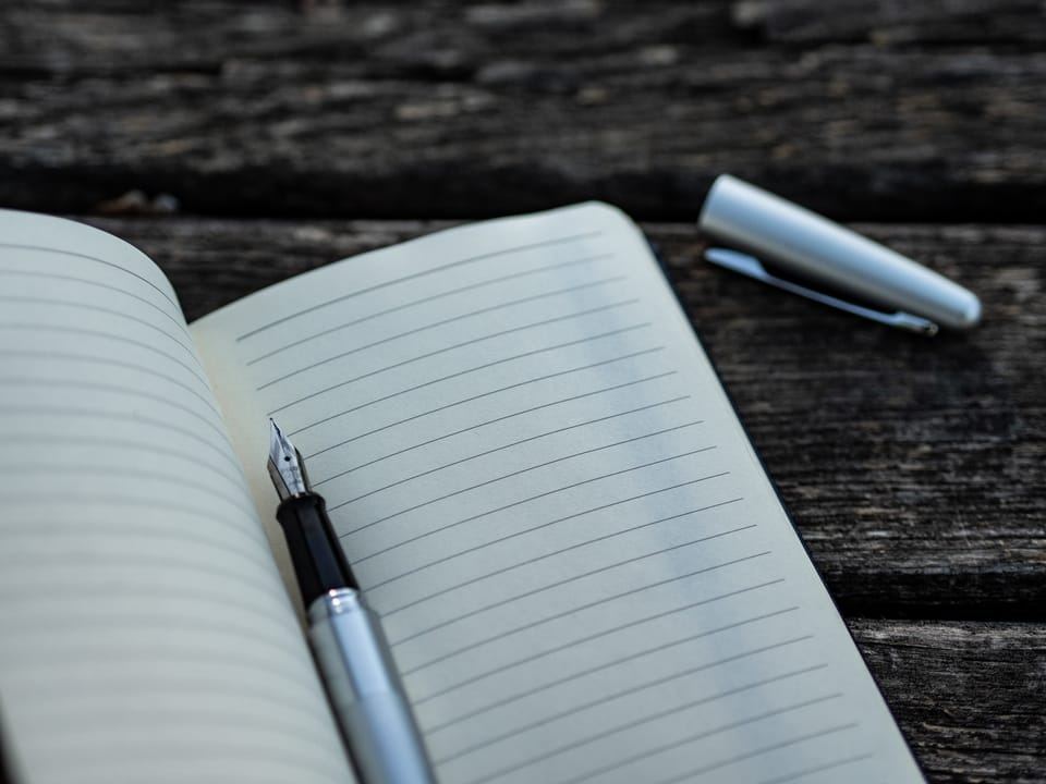 white notebook with black pen inside